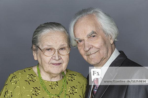 Porträt eines glücklichen älteren Paares über grauem Hintergrund