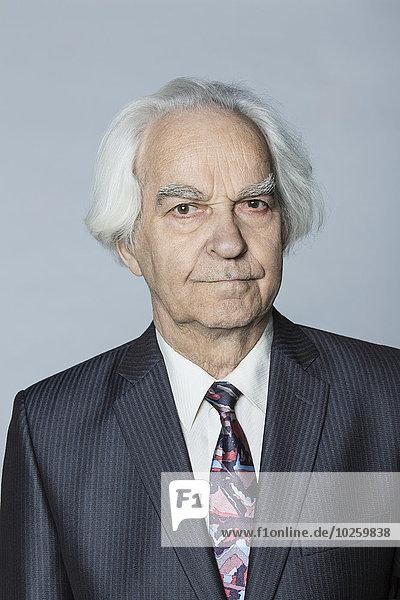 Porträt eines selbstbewussten älteren Mannes vor grauem Hintergrund