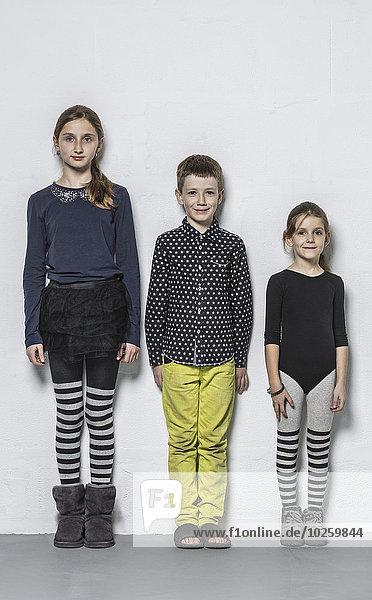 Ganzflächiges Porträt eines lächelnden Bruders mit nebeneinander stehenden Schwestern an der Wand