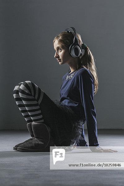 Durchgehende Seitenansicht des Mädchens beim Musikhören über Kopfhörer über grauem Hintergrund