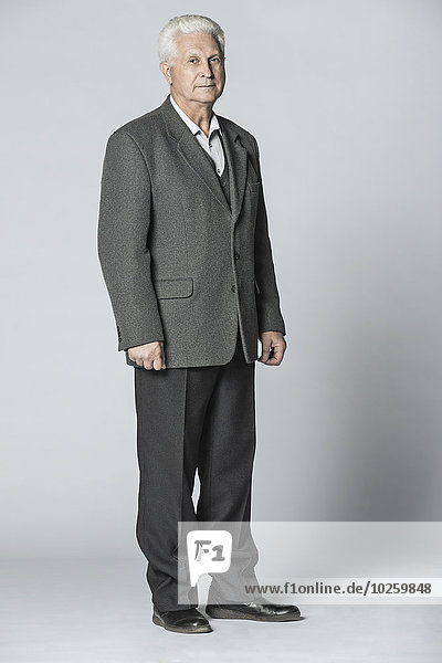 Vollständiges Porträt eines selbstbewussten älteren Mannes über grauem Hintergrund