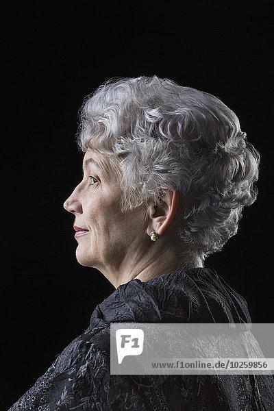 Seitenansicht der Seniorin über schwarzem Hintergrund