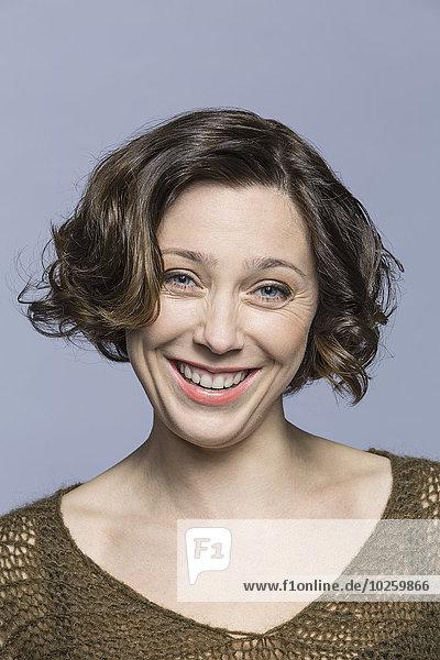 Porträt einer lächelnden mittleren erwachsenen Frau über grauem Hintergrund