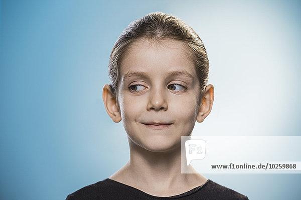 Süßes Mädchen schaut seitwärts über blauem Hintergrund