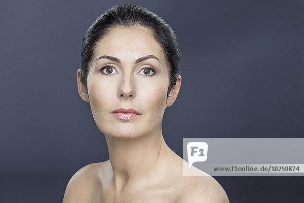 Nahaufnahme des Porträts einer oben ohne reifen Frau über grauem Hintergrund