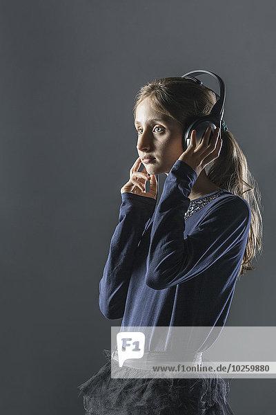 Nachdenkliches Mädchen  das Musik über Kopfhörer über grauem Hintergrund hört.