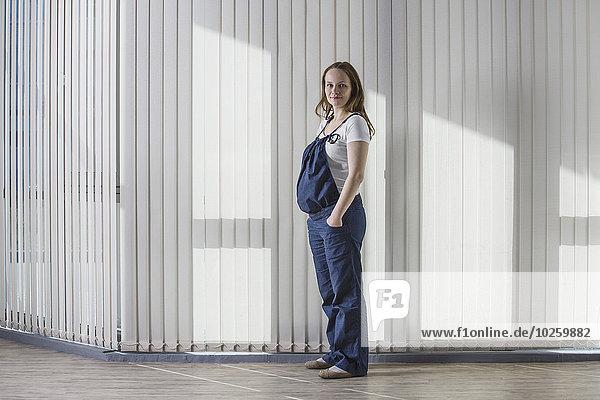 Ganzkörperporträt einer schwangeren Frau im Overall gegen den Vorhang stehend