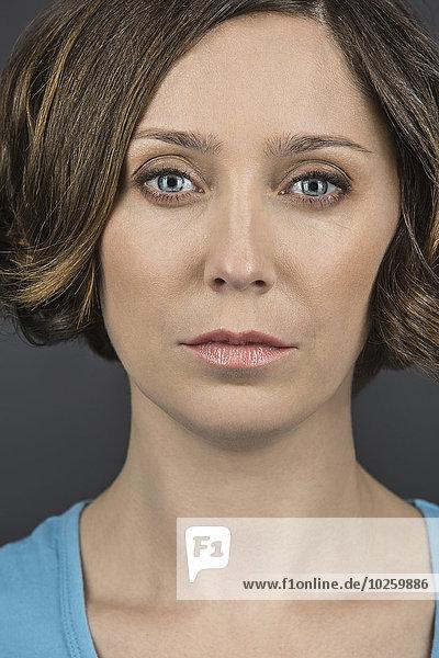 Porträt einer ernsthaften mittelgroßen Frau über grauem Hintergrund