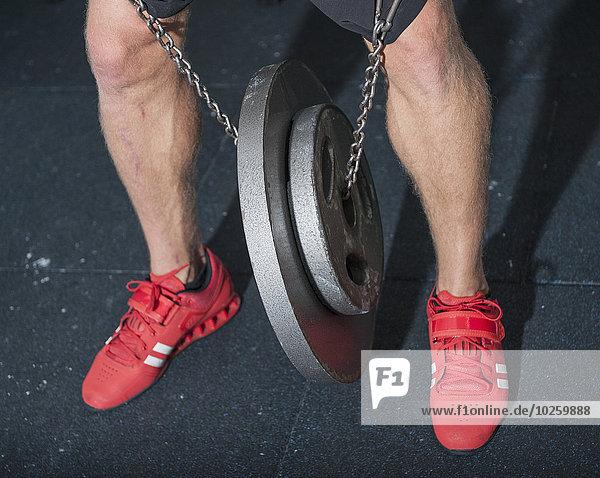 Niedrige Sektion des Mannes mit Gewichten in der Turnhalle