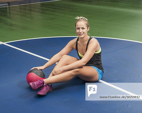 Ganzkörperporträt einer Frau mit Medizinball in der Turnhalle