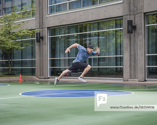 Volle Länge des jungen Mannes  der gegen den Turnhallenbau läuft.
