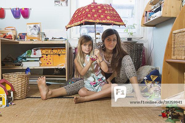 sitzend,Portrait,Fröhlichkeit,Boden,Fußboden,Fußböden,Regenschirm,Schirm,halten,Tochter,Parkett,Mutter - Mensch