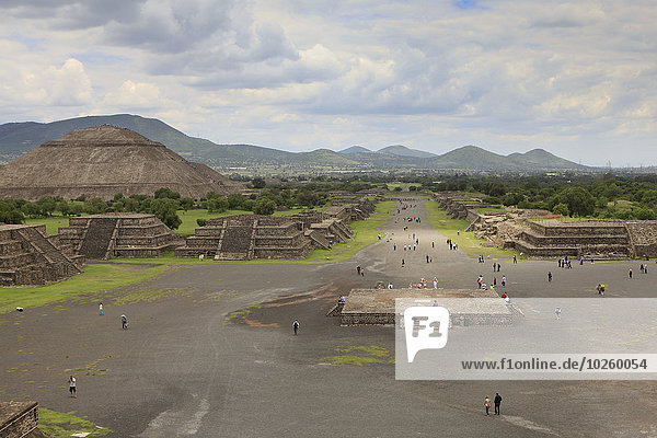 Hochwinkelansicht der Menschen auf der Straße durch die Sonnenpyramide gegen den bewölkten Himmel