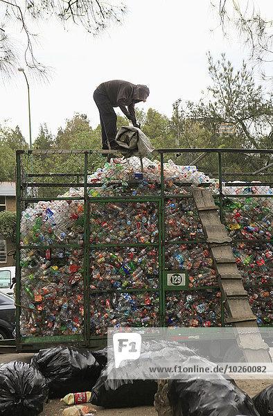 Mann  der auf der Mülldeponie an einem Haufen wiederverwertbarer Plastikabfälle arbeitet.