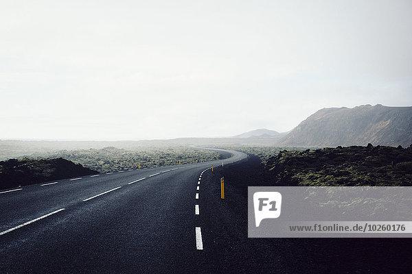 Landstraße am Berg vorbei gegen den klaren Himmel