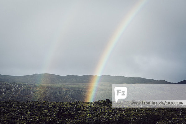 Regenbogen über den Bergen gegen den Himmel