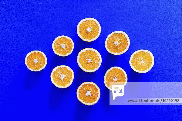 Direkt über der Aufnahme von Orangenscheiben in Rautenform auf blauem Grund angeordnet