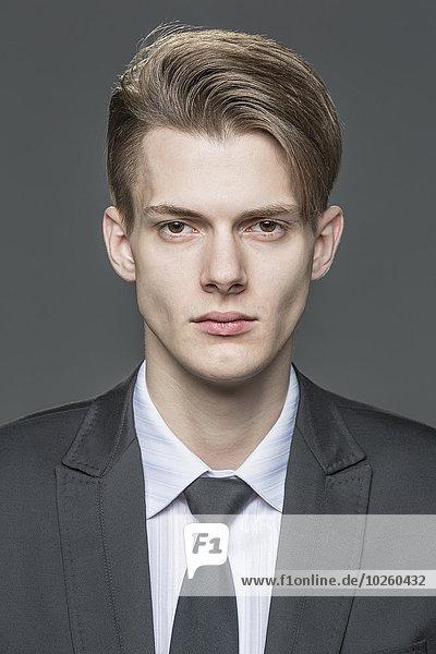 Porträt eines selbstbewussten jungen Geschäftsmannes über grauem Hintergrund