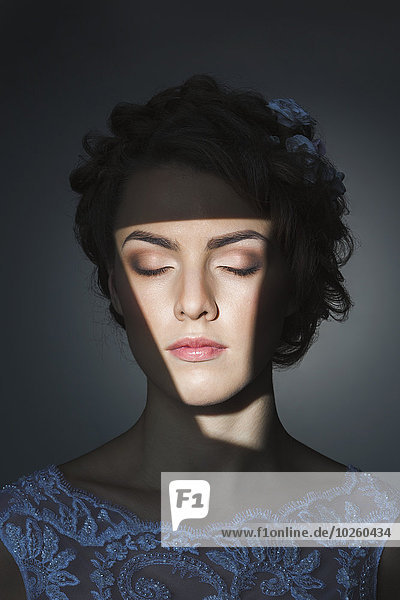 Schöne junge Frau mit geschlossenen Augen über grauem Hintergrund