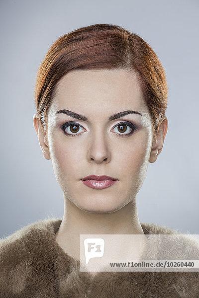Porträt der selbstbewussten jungen Frau über grauem Hintergrund