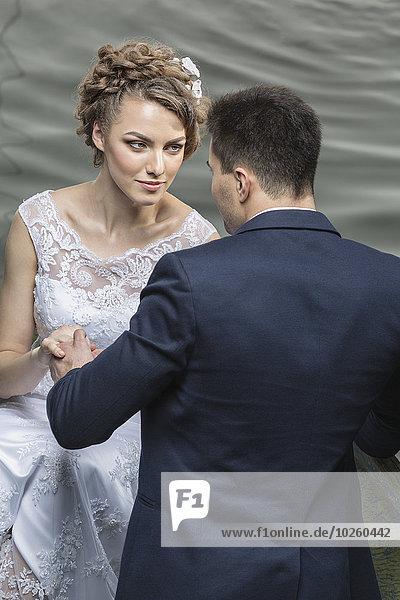 Junges Brautpaar hält sich am Seeufer an den Händen