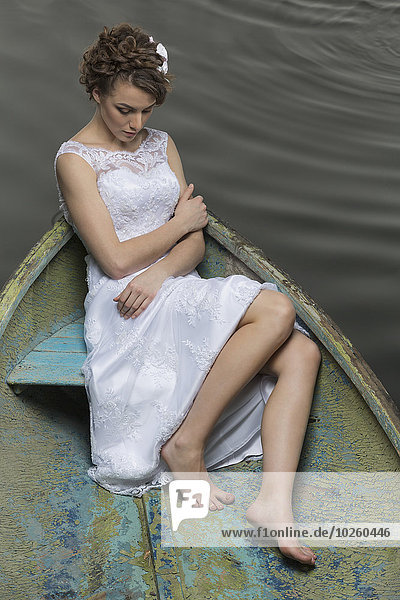 Volle Länge der jungen Braut im Boot auf dem See sitzend