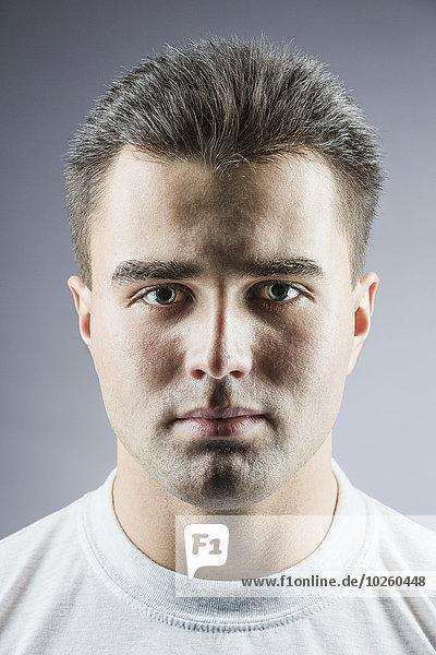 Porträt eines hübschen jungen Mannes über grauem Hintergrund