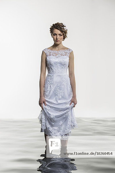Porträt einer jungen Braut  die im Wasser vor weißem Hintergrund steht.