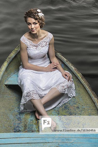 Hochwinkelporträt einer jungen Braut im Boot auf dem See