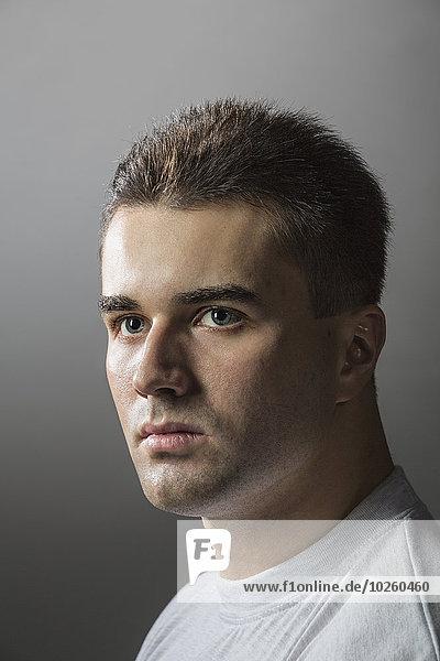 Nahaufnahme eines nachdenklichen jungen Mannes vor grauem Hintergrund