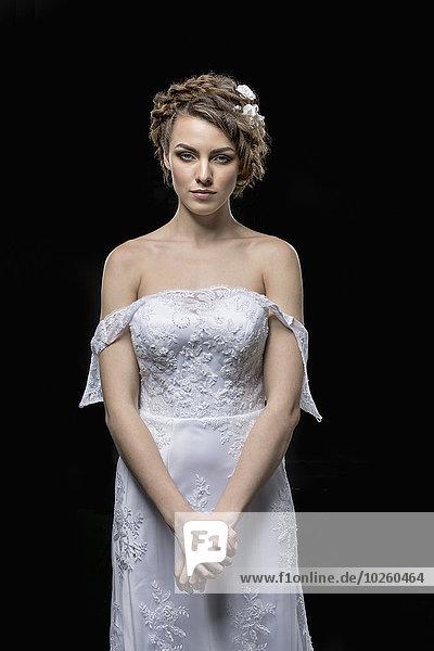 Porträt einer ernsthaften jungen Braut auf schwarzem Hintergrund