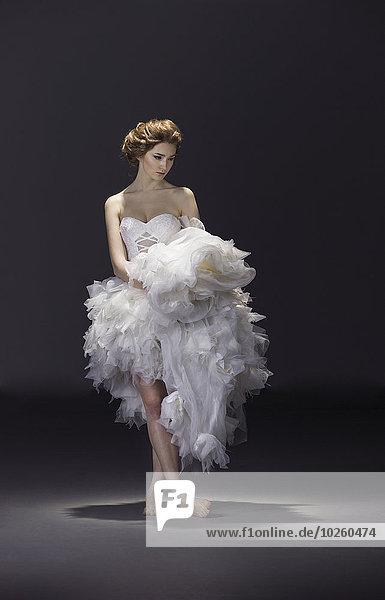 Volle Länge der jungen Braut im Brautkleid stehend über farbigem Hintergrund