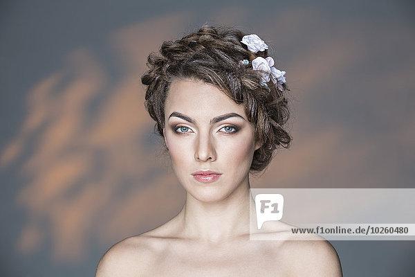 Porträt der schönen jungen Frau an der Wand