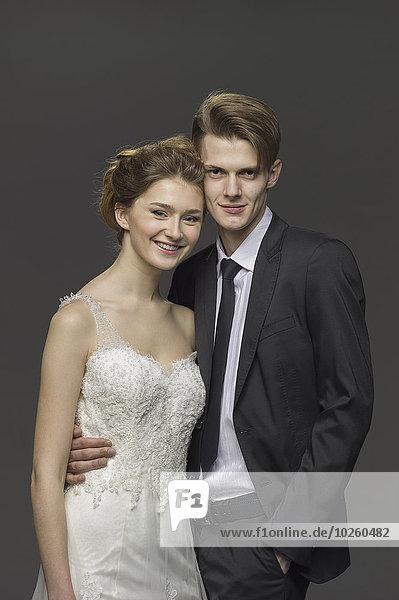 Porträt eines glücklichen Brautpaares vor grauem Hintergrund