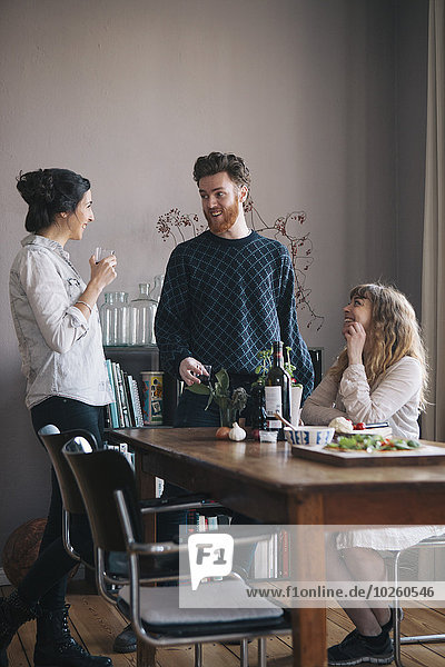 Junger Mann mit Freundinnen beim Frühstück zu Hause