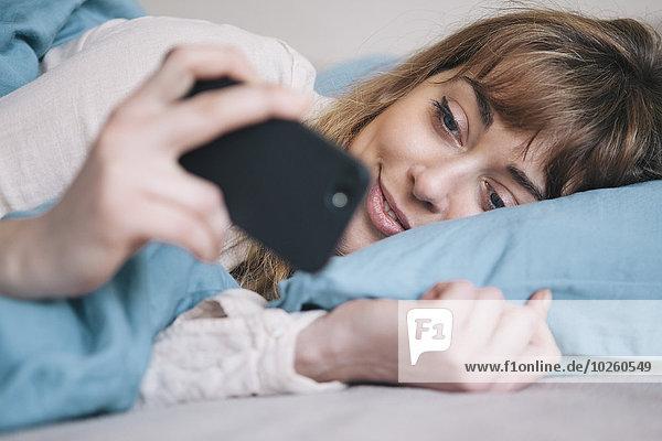 Handy,junge Frau,junge Frauen,benutzen,Entspannung,Bett,Kurznachricht