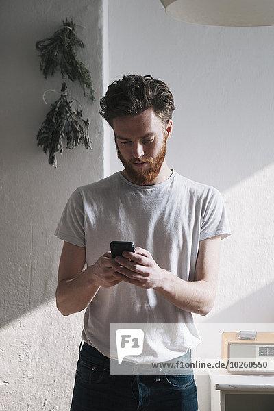 Junger Mann mit Handy zu Hause