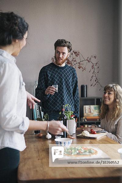 Junger Mann mit weiblichen Freunden beim Frühstücken zu Hause