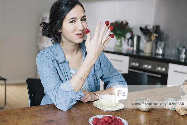 Porträt einer glücklichen jungen Frau  die zu Hause Himbeeren an den Fingern hält.