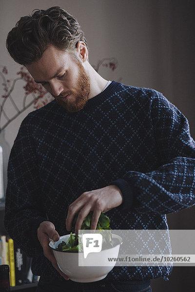 Junger Mann macht Gemüsesalat in der Küche