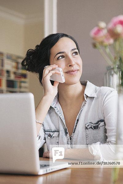 Schöne junge Frau mit Handy mit Laptop auf dem Tisch zu Hause