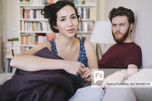 Porträt einer jungen Frau mit einem Mann  der sich im Bett entspannt.