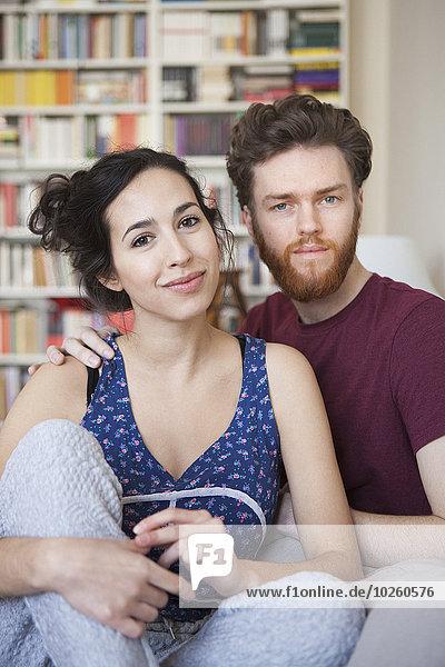 Porträt einer jungen Frau mit einem Mann  der sich zu Hause entspannt.
