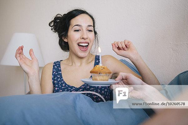 Überraschte junge Frau bläst Kerze auf Muffin  die der Mann zu Hause hält.