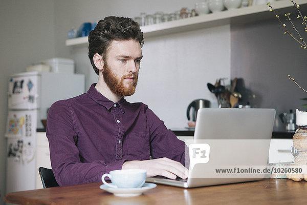 Sicherer junger Mann mit Laptop am Tisch in der Küche