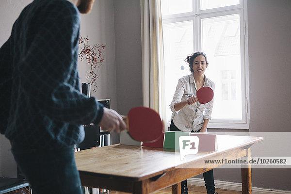 Junge Frau beim Tischtennisspielen mit Mann zu Hause