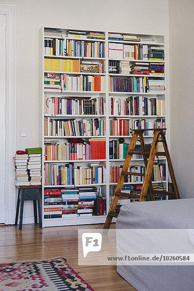Stufenleiter in der Nähe von Bücherregalen zu Hause