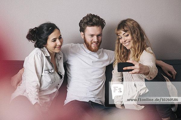 Junge Freunde nehmen Selfie durch Smartphone im Wohnzimmer mit