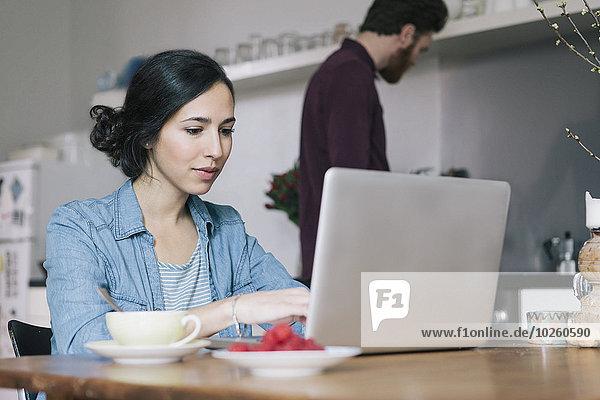 Junge Frau mit Laptop und Mann im Hintergrund in der Küche