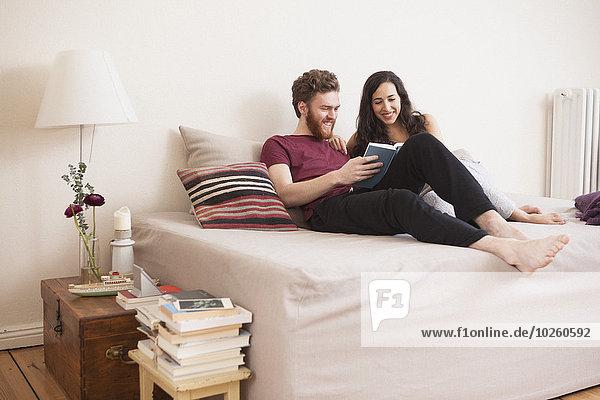 Glücklicher junger Mann liest Buch für Frau im Bett